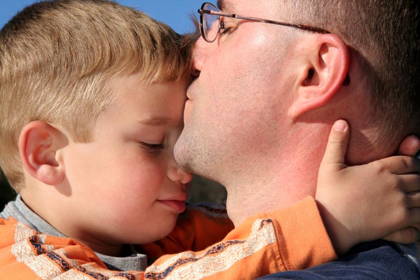 Dad kissing son