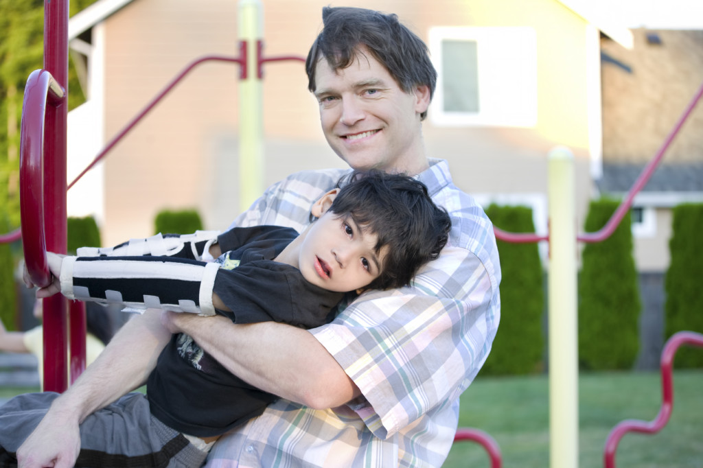 Father helping disabled son to play at playground