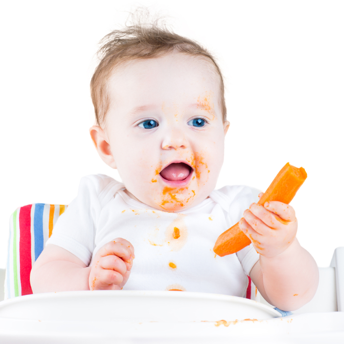 Baby eating carrot