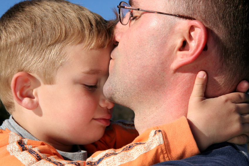 Dad kissing son