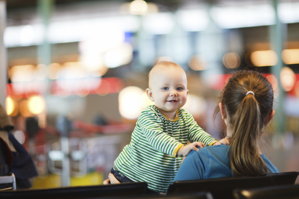 Mother and baby daughter waiting their flight at airport