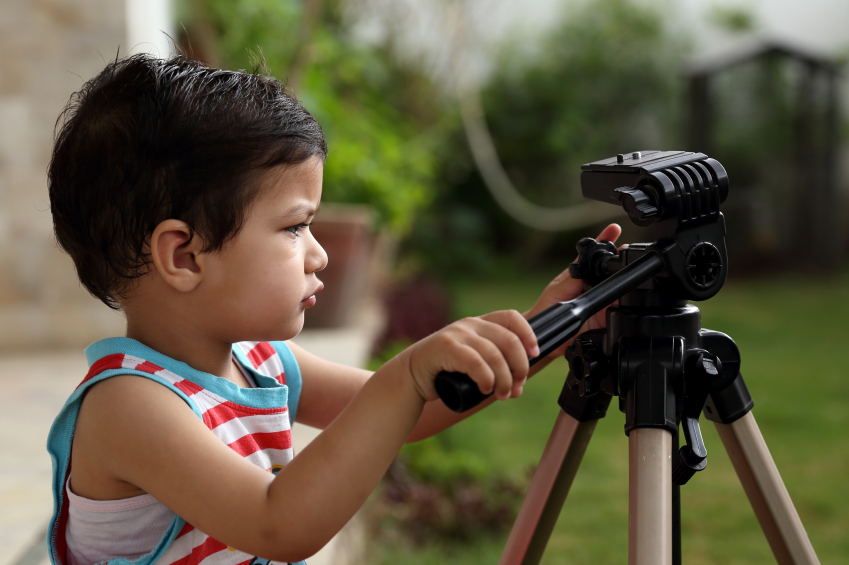 Kid trying his hands on a tripod